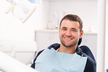 man sitting in dental exam chair smiling l dentist 30566
