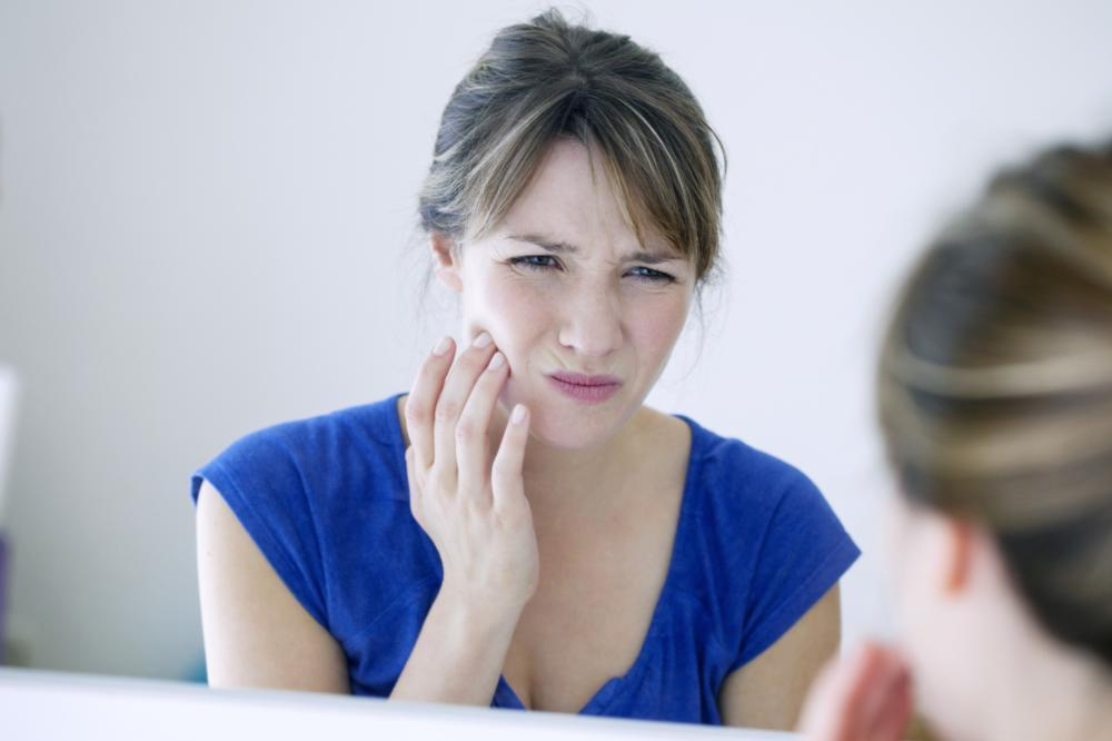 woman holding her jaw | emergency dentist flowery branch ga