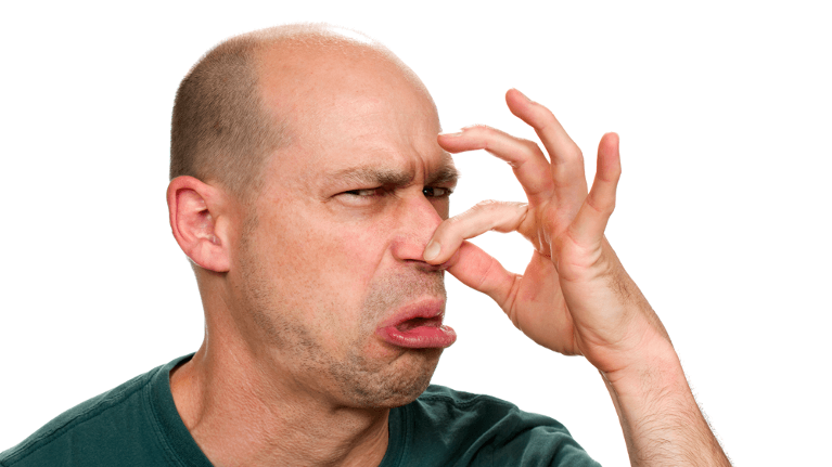 man plugging his nose in disgust | dentist in flowery branch ga