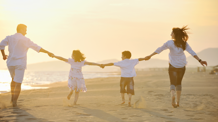 family holding hands on the beach | family dentist flowery branch ga