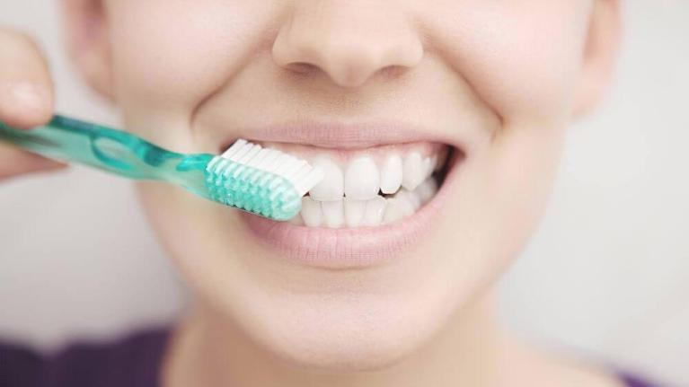 woman brushing teeth | family dentistry flowery branch ga