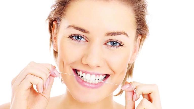 woman flossing | dental crown flowery branch ga