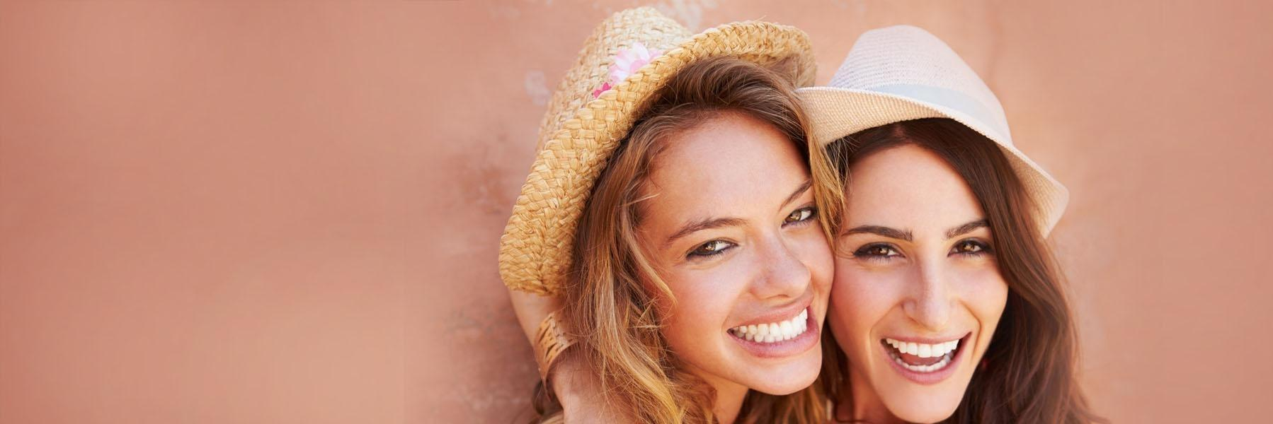 Two women with hats smiling l 30566 Dentist